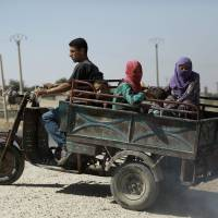 Syrian Kurds flee reported shelling in Hassakeh on Thursday. | AFP-JIJI
