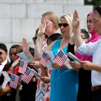 People are sworn in at a naturalization ceremony for new U.S. citizens at the WWII Memorial in Washington on Thursday.   REUTERS