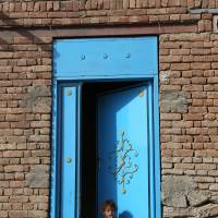 An Afghan girl sits at the entrance to her home on the outskirts of Kabul Sunday.   AP