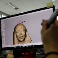 An employee works on 3-D rendering at a specialist printing company in Seoul on Friday. | REUTERS