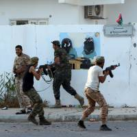 Forces loyal to Libya's U.N.-backed Government of National Accord (GNA) hold a position near the central area known as District One on Sunday as they fight Islamic State group jihadis holed up in the coastal city of Sirte, east of the capital Tripoli. | AFP-JIJI