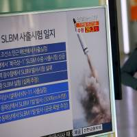 A pedestrian passes a TV screen showing a news report about a ballistic missile fired from a North Korean submarine, at a railway station in Seoul on Aug. 24. | REUTERS