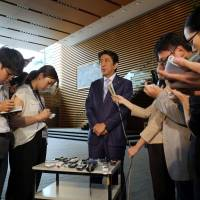 Prime Minister Shinzo Abe speaks to reporters at his official residence in Tokyo on Wednesday following a ballistic missile launch by North Korea that landed 250 kilometers (155 miles) off Japan's coast, calling it an 'outrageous act' that posed a serious threat. | AFP-JIJI