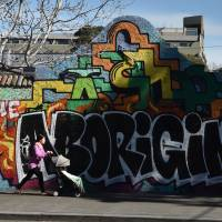 A woman pushes a baby past a graffiti wall with the words 'The Aboriginal' in reference to Australia's indigenous people on Wednesday. | PETER PARKS / AFP-JIJI