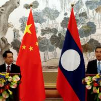 Laos Foreign Minister Saleumxay Kommasith (left) and his Chinese counterpart, Wang Yi, hold a news conference after a meeting at the Diaoyutai State Guesthouse in Beijing on Aug. 3. | REUTERS