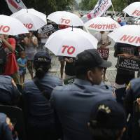 Filipino police block protesters holding umbrellas and posters with slogans as they protest outside a hotel in Manila on Tuesday against using nuclear energy in the country. | AP