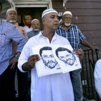 At the front entrance of the Al-Furqan Jame Masjid mosque in the Ozone Park section of Queens, New York, a police sketch of a suspect believed to have shot the mosque's Imam is displayed by members of the mosque Sunday, a day after 55-year-old Imam Maulama Akonjee and his 64-year-old associate, Thara Uddin, were shot in the back of the head after they left the mosque following afternoon prayers Saturday. | AP