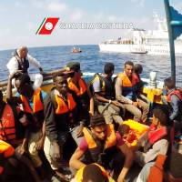 This image grab taken from a handout video and released by the Italian coast guard (Guardia Costiera) on Tuesday shows Italian coast guard personnel taking part in a rescue operation of a boat with migrants in the Mediterranean Sea. | GUARDIA COSTIERA / HO / AFP-JIJI