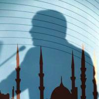 The shadow of Turkish President Recep Tayyip Erdogan falls across a painting of a mosque as he addresses the Turkish Religious Affairs Directorate in Ankara on Wednesday. | AP