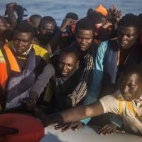 About 150 sub-Saharan refugees and migrants receive life jackets Saturday as they board an overcrowded rubber boat and wait to be assisted by an NGO during a rescue operation on the Mediterranean Sea, about 23 km (14 miles) north of Sabratha, Lybia. | AP