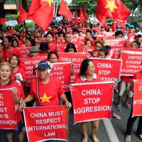 Filipino and Vietnamese activists display placards during a rally over the South China Sea disputes in front of a Chinese Consulate in Makati city, metro Manila, on Saturday. | REUTERS