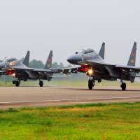 Two Chinese Su-30 fighter jets take off from an unspecified location to for patrol over the South China Sea in this undated photo released Saturday. | XINHUA / VIA AP