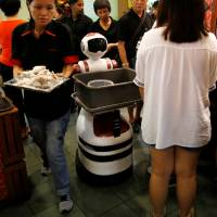 A robot collects dirty dishes at Chilli Padi Nonya Cafe in Singapore on July 6. | REUTERS