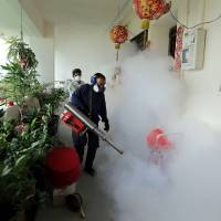 This Sunday photo made available by the Straits Times shows workers fogging in the housing estate at Aljunied Crescent in Singapore. | AFP-JIJI