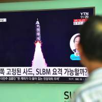 A man watches a TV report about North Korea's latest submarine-launched ballistic missile test on a screen set up at a railway station in Seoul last Thursday. | AFP-JIJI