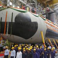 Workers pose beneath the Indian Navy's first Scorpene submarine ahead of its launch in Mumbai in April 2015. | REUTERS