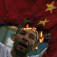 A protester burns the national flag of China during an anti-Syrian regime protest in front of the Arab League headquarters in Cairo in October 2011.   AP