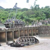 A CM11 armoured vehicle lies upside down in a river, killing four of the five soldiers inside, in southern Pingtung, Taiwan, Tuesday. The soldiers were killed when the tank slipped and plunged into the river during heavy rains following an annual firing drill in southern Taiwan. | AFP-JIJI