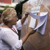 A Thai woman checks names at a polling station in Bangkok on Sunday. Thais headed to the polls for the first time since the army grabbed power in 2014 in a referendum on a new military-drafted constitution. | AFP-JIJI