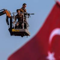 Turkish special forces police officers stand guard as people wave national flags on Sunday during a rally in Istanbul against the July 15 failed military coup. | AFP-JIJI