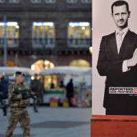 A French soldier walks past a poster of Syrian strongman Bashar Assad showing off his middle finger in Strasbourg, France, last November. The poster was sponsored by the nonprofit organization Reporters Without Borders. | AFP-JIJI