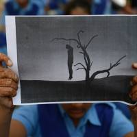 An Indian schoolgirl holds an image of a hanged man during a rally in Ahmedabad in December 2012 after the victim of a brutal New Delhi gang-rape died.   AFP-JIJI