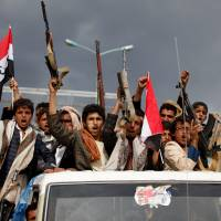 Armed men ride on the back of a truck in Sanaa on Aug. 1 to attend a rally held by supporters of Houthi rebels and Yemen's former President Ali Abdullah Saleh following an agreement reached by Saleh and the Houthis to form a political council to unilaterally rule the country.   REUTERS