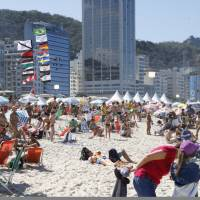 Beach-goers soak up the rays on Copacabana Beach, the site of the beach volleyball tournament at the Rio Olympics, on Aug. 13. | KYODO