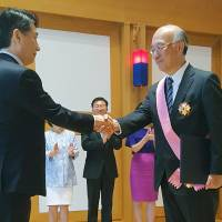 Japanese Ambassador to the United Nations Koro Bessho (right) is awarded South Korea's top diplomatic medal at Seoul's mission to the U.N. in New York on Friday. | KYODO