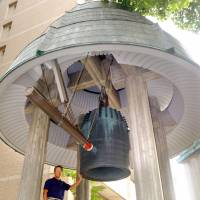 Toshihiko Yamada stands by a bell that rings out three times a day in the Osaka neighborhood of Tsuriganecho. He and other volunteers look after the ancient landmark. | KYODO