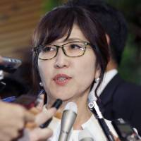 Newly appointed Defense Minister Tomomi Inada answers questions from reporters at the prime minister's official residence in Tokyo on Wednesday. | AP