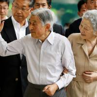 Emperor Akihito and Empress Michiko wave to well-wishers as they board a bullet train for their summer villa in Nasu, Tochigi Prefecture, at Tokyo Station on July 25. | REUTERS