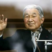 Emperor Akihito waves to well-wishers gathered at the Imperial Palace to mark his 82nd birthday in Tokyo on Dec. 23. | REUTERS