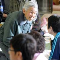 Emperor Akihito speaks to people affected by the March 2011 Tohoku disasters at an evacuation center in Kamaishi, Iwate Prefecture, in May of that year. | KYODO