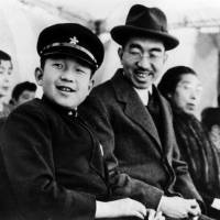 Crown Prince Akihito sits with his father, Emperor Hirohito, posthumously known as Emperor Showa, as they watch a sports event put on by Imperial Household staff at the Imperial Palace in Tokyo in April 1947. | IMPERIAL HOUSEHOLD AGENCY / VIA KYODO