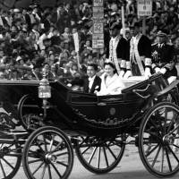 Crown Prince Akihito and Crown Princess Michiko ride in a carriage through a cheering crowd in Tokyo following their wedding ceremony on April 10, 1959. | KYODO