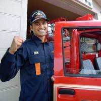 Bhushan Hastak, a member of a municipal volunteer fire corps, poses for a photo in Misato, Miyagi Prefecture, in July. | KYODO