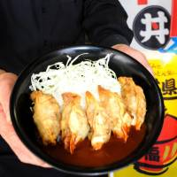 Toshikazu Watanabe, a restaurant owner in the city of Fukui, displays a bowl of fish gyoza (dumplings) with demiglace sauce, one of the otomashii don inventions on his menu. | KYODO
