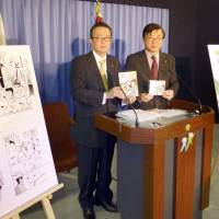 Hajime Funada (left) presents a comic book that gives reasons to revise the Constitution, at the Liberal Democratic Party's headquarters in Tokyo on April 28. | KYODO