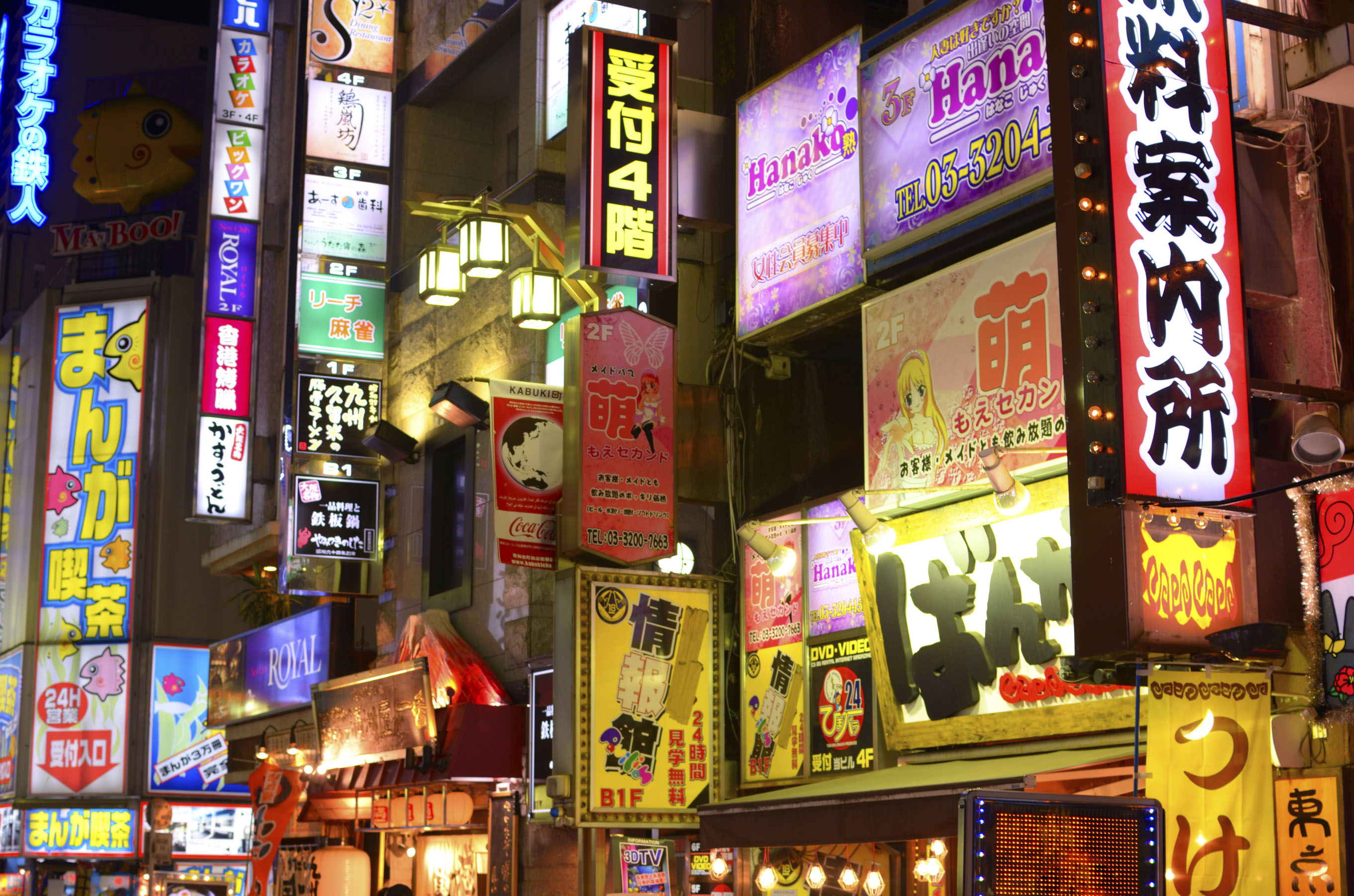 Neon signs for sex industry venues are seen among the bars and clubs in Tokyo's Kabuki-cho red light district. Economic hardship is pushing many middle-aged women toward the nation's sex industry, despite the stigma and physical risk. | SEAN PAVONE PHOTO