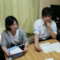 Lawyer Reia Tokuda (left) and social worker Hirofumi Oikawa listen to a woman in the call girl industry discuss her financial problems at a free consultation run by the Fu Terasu project on July 2, in a tiny apartment in Tokyo. | TOMOHIRO OSAKI
