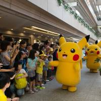 Performers dressed as Pikachu interact with children as they march through a shopping mall during the Pikachu Outbreak event in Yokohama on Aug. 7 last year. | BLOOMBERG