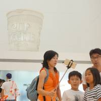 Visitors take selfies below a giant replica of Cup Noodles displayed at the Cup Noodles Museum in Yokohama on Aug. 15. | SHUSUKE MURAI