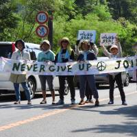 Demonstrators block the road in the Takae district of the village of Higashi in Okinawa Prefecture, holding Japanese signs saying 'Protect the Yanbaru (jungle).' | JON MITCHELL
