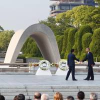 Prime Minister Shinzo Abe (left) shakes hands with U.S. President Barack Obama after laying wreaths at Hiroshima Peace Memorial Park on May 27. | POOL / VIA KYODO