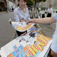 A woman picks up a newspaper extra Monday in Tokyo featuring Ichiro Suzuki getting his 3,000th career base hit. | KYODO