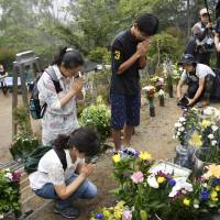 People pray in front of a stone monument commemorating the victims on Osutaka Ridge in Gunma Prefecture, where the Japan Airlines Boeing 747 slammed into the ground 31 years ago. | KYODO