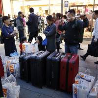 Tourists won't have to carry their suitcases while traveling in Japan anymore under an upcoming service that requires their precise itinerary details be submitted for conversion into barcodes in advance. | BLOOMBERG