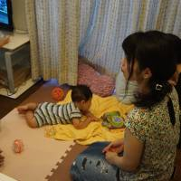 Two mothers, one of whom is a resident of shared house Codona HAUS in Tokyo's Suginami Ward, discuss their children during a community meal. The facility has four bedrooms set around a shared kitchen and living room. | MAGDALENA OSUMI