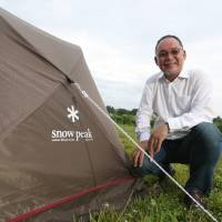 Toru Yamai, president and chief executive officer of Snow Peak, Inc., poses next to his company's tent at the Snow Peak Headquarters Camp Field in Sanjo, Niigata Prefecture, on Aug. 2.   BLOOMBERG